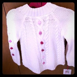 White sweater with pink Pom poms
